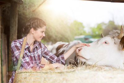 Smiling woman caring for a cow on a farm
