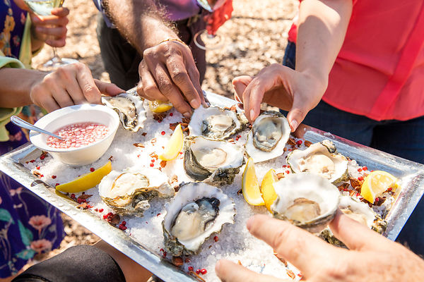 People eating freshly shucked oysters from a commercial photoshoot for Kendal Jackson Wine Company
