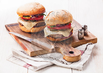 Burger with meat on cutting board on white wooden background