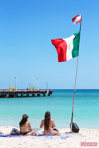 Young women at the beach near mexican flag, Mexico