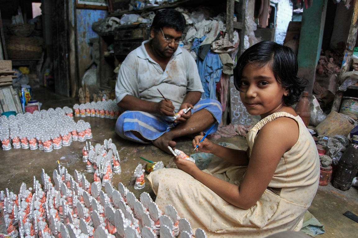 A girl and her father paint religious idols in their home workshop im Bhawanipur, Kolkata, India
