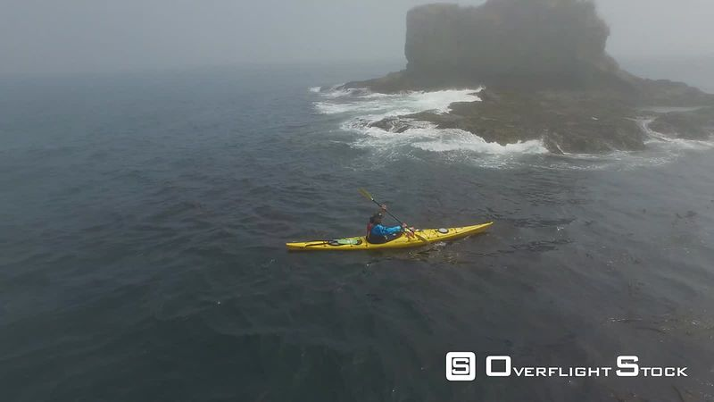 Lone sea kayaker near freshwater bay on foggy day Washington State