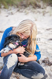 Blonde girl hugging small chihuahua mix breed dog on the beach