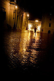 An atmospheric image of a man at night on a rainy cobbled street in Rome, Italy.
