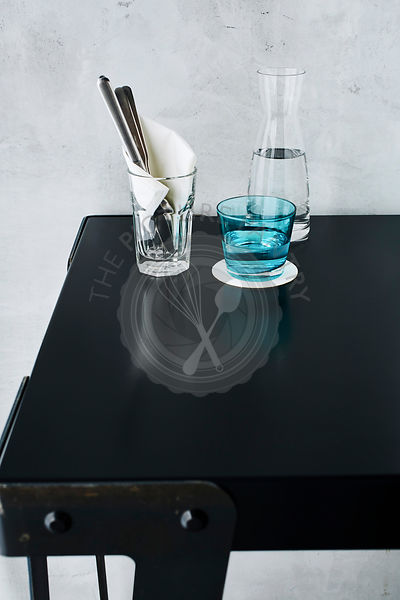 Blue glass of water with carafe on a restaurant table