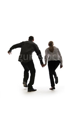 A man and a woman running hand in hand, from behind – shot from eye level.