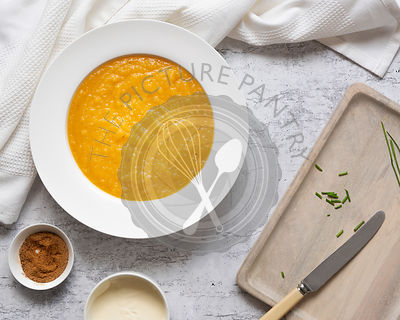 A bowl of homemade pumpkin soup beside small bowls of nutmeg and cream and chives on a wooden cutting board.