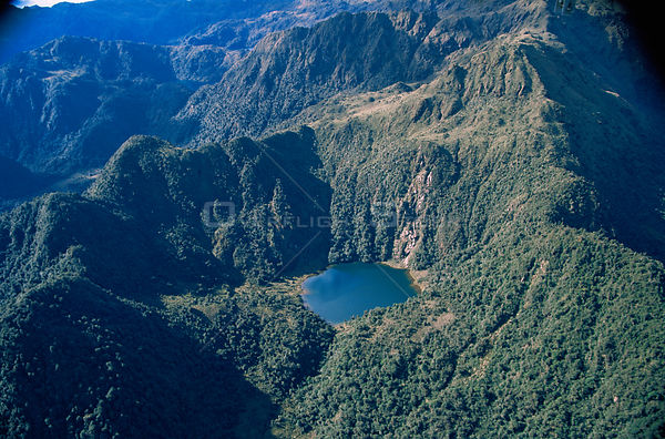 Aerial view of lake amongst tree covered mountains, Peru, South America  2000
