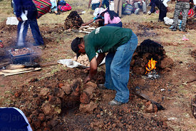 Man making a huatia or earth oven , near Cusco , Peru