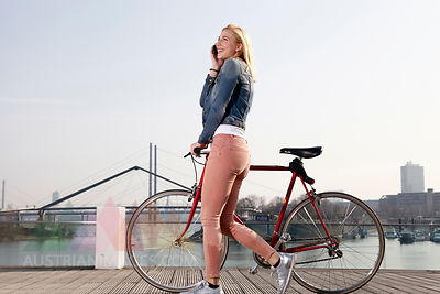 Germany, Duesseldorf, happy blond woman with bicycle and smartphone in front of Rhine River