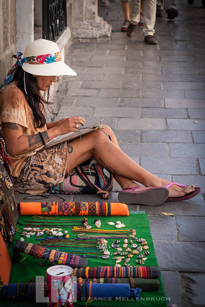 Young women selling and making her creations on a street in Cuzco, Peru