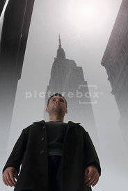 An atmospheric image looking up at a man in a misty New York City.