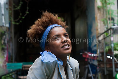 Headshot of young curly woman looking up in urban surrounding
