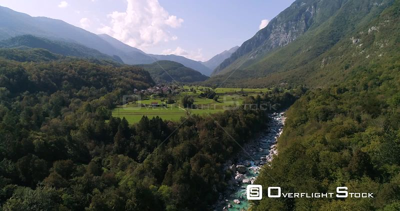 Alpine rapids, C4K aerial drone view over turquoise soca river, towards a small town, in the alp nature, near Trigolov nation...