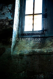 A dirty window letting light into a damp and decaying prison cell.