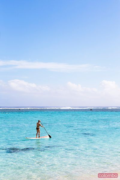 Woman stand up paddling in Rarotonga, Cook Islands