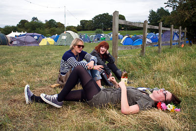 UK - Standon - Three women friends joke and laugh in a field next to a mobile sound system at the Standon Calling Festival
