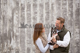 couple holding and smiling at small dog with barnwood wall