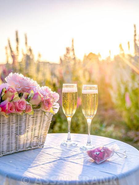 Champagne glasses and a basket of flowers on a table in a field at sunset