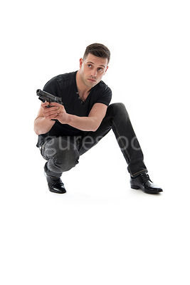 A mystery man, crouching, with a gun – shot from low level.