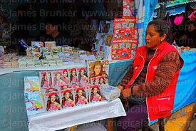 Woman selling miniature fashion magazines on stall, Alasitas festival, La Paz, Bolivia