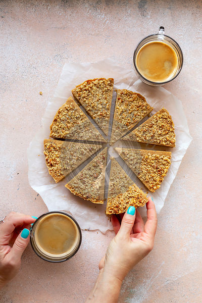Young female having a walnut shortbread cookie and a cup of coffee for breakfast