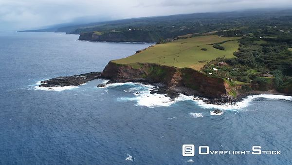 Orbiting green pastureland on sea cliffs along Maui's north shore.