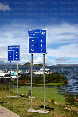 Signs to Amantani and Taquile Islands in port, Lake Titicaca, Puno, Peru