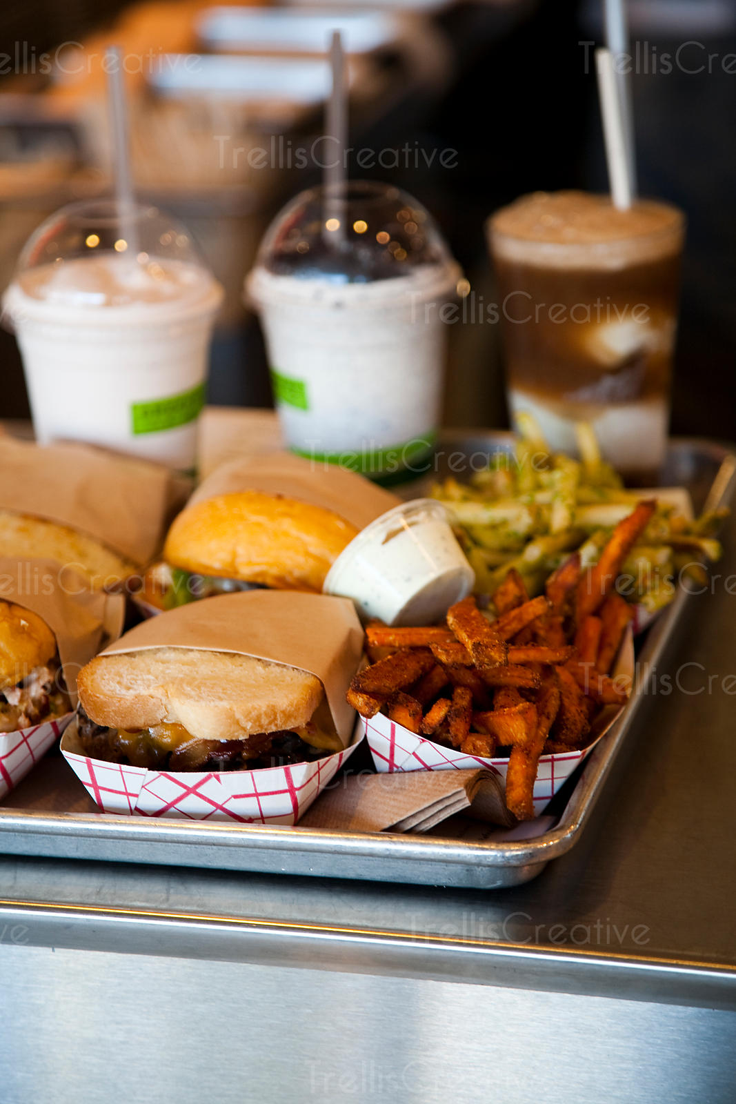A tray of burgers and milk shakes at a diner