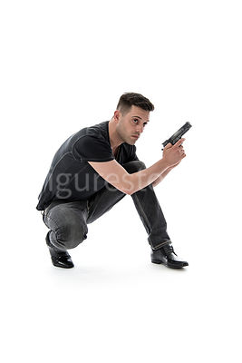 A mystery man, crouching, with a gun – shot from mid level.