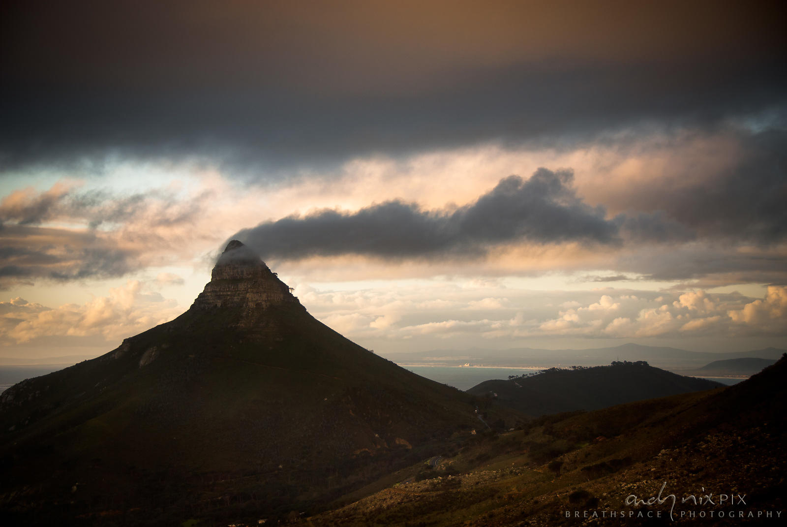 Silhouette of Lions Head with a cloud blowing off the summit, blue sky and clouds behind