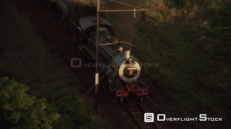 Aerial shot of steam train traveling along the tracks through lush green vegetation Johannesburg Gauteng South Africa