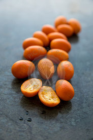 scattering of vibrant orange backlit kumquats, on green marble background