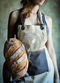 Young woman holding in her hand a fresh loaf of italian bread