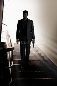 An atmospheric image of a mystery man with a gun, walking down some steps, in a stairwell.