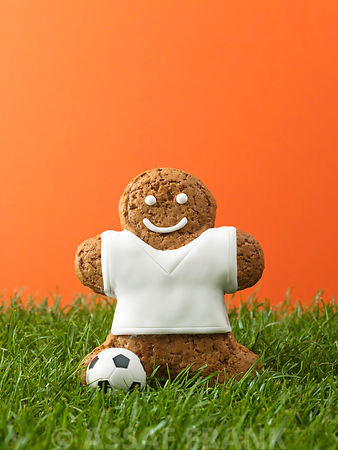 Gingerbread man with football on grass