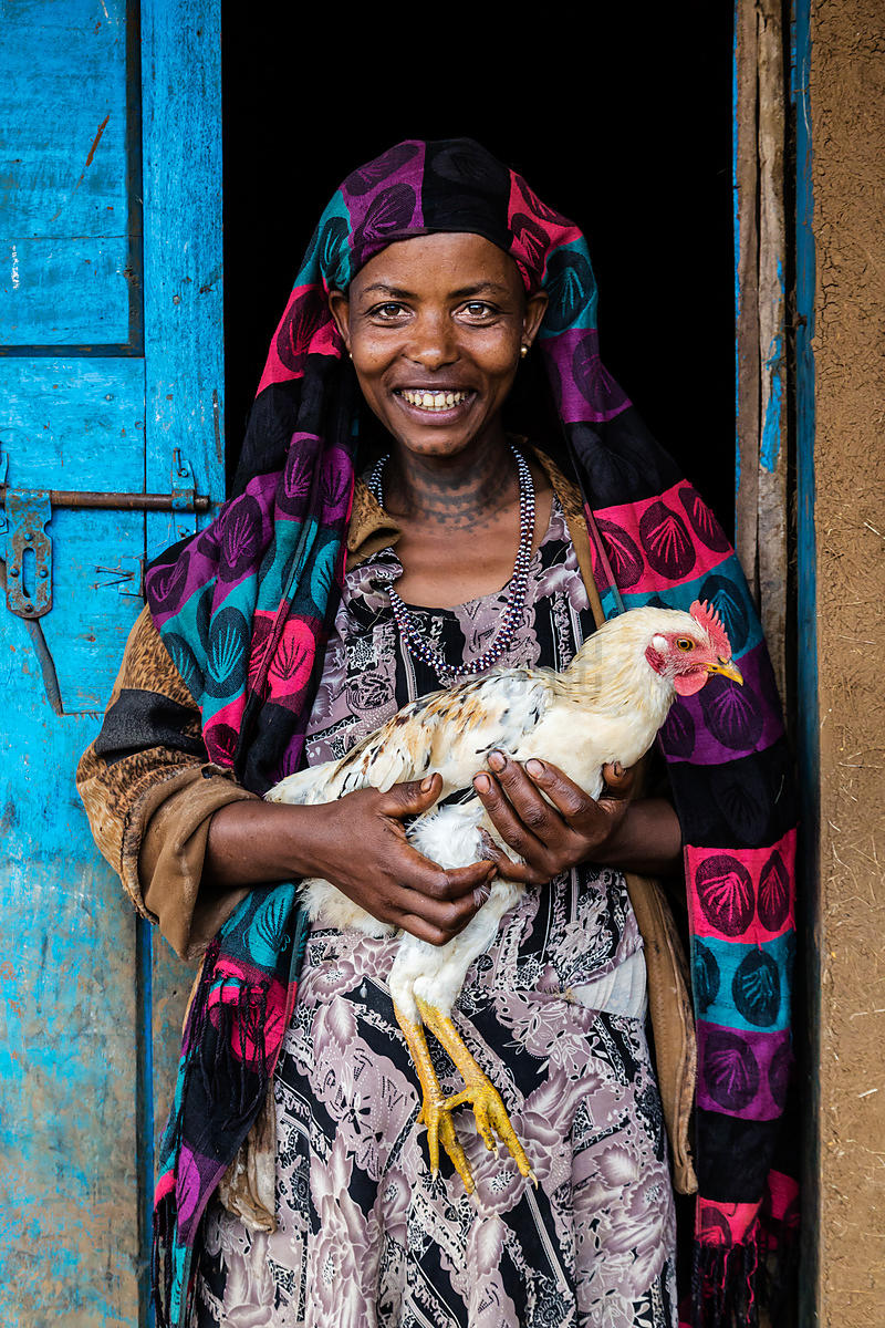 Woman Holding Chicken in the Door of Her Home