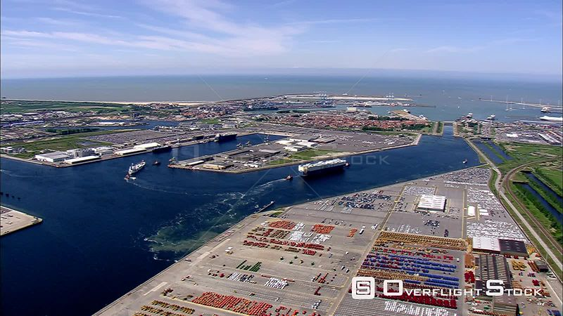 Flying over a port and tugboats guiding a cargo ship into a berth