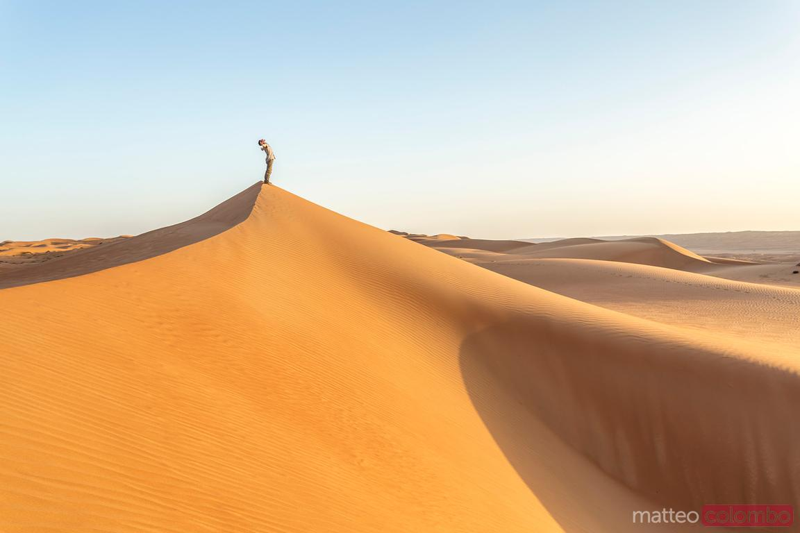 Tourist on the sand dunes of Wahiba Sands, Oman