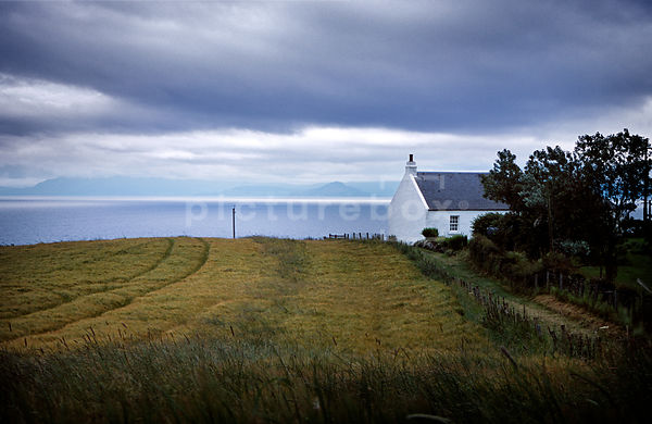 A landscape image of a house on a loch in the countryside, taken in Scotland.