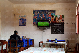 Man watching football on television while having lunch, Villa Abecia, Chuquisaca Department, Bolivia