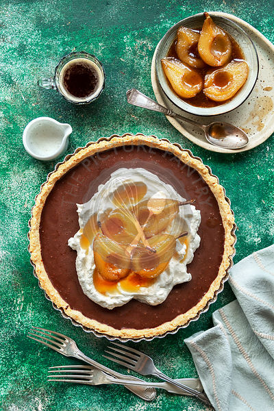 Chocolate tart topped with whipped cream and roasted pears