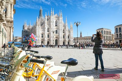 Woman taking a photo of the famous Duomo, Milan, Italy
