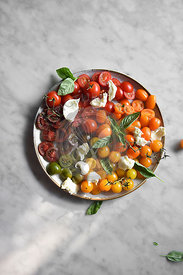 Various tomatoes in the sunlight on a marble background