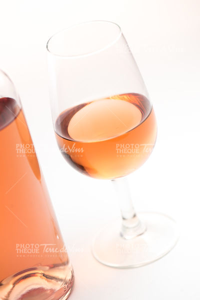 Rose wine glass and bottle on white background