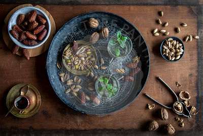 Healthy teatime oriental style with mint tea, dates, walnuts and pistachios  on black ornamental tray over wooden background
