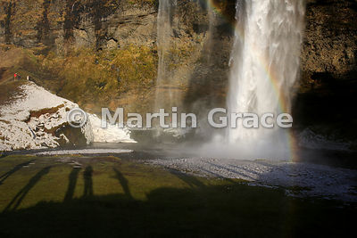 Seljalandsfoss waterfall in late winter with long shadows of tourists, Iceland south coast