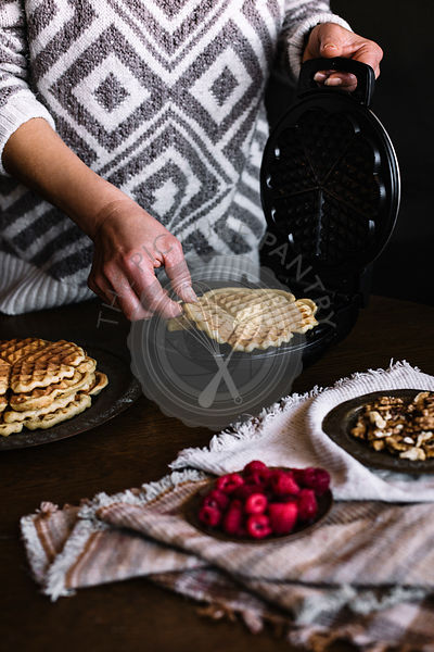 WOMAN IS MAKING DELICIOUS WAFFLES