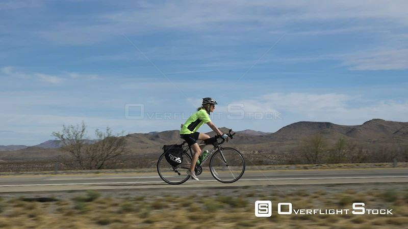Side profile shot of person cycling alongside Highway I10, Sierra Blanca, Texas, USA. Parallax effect.