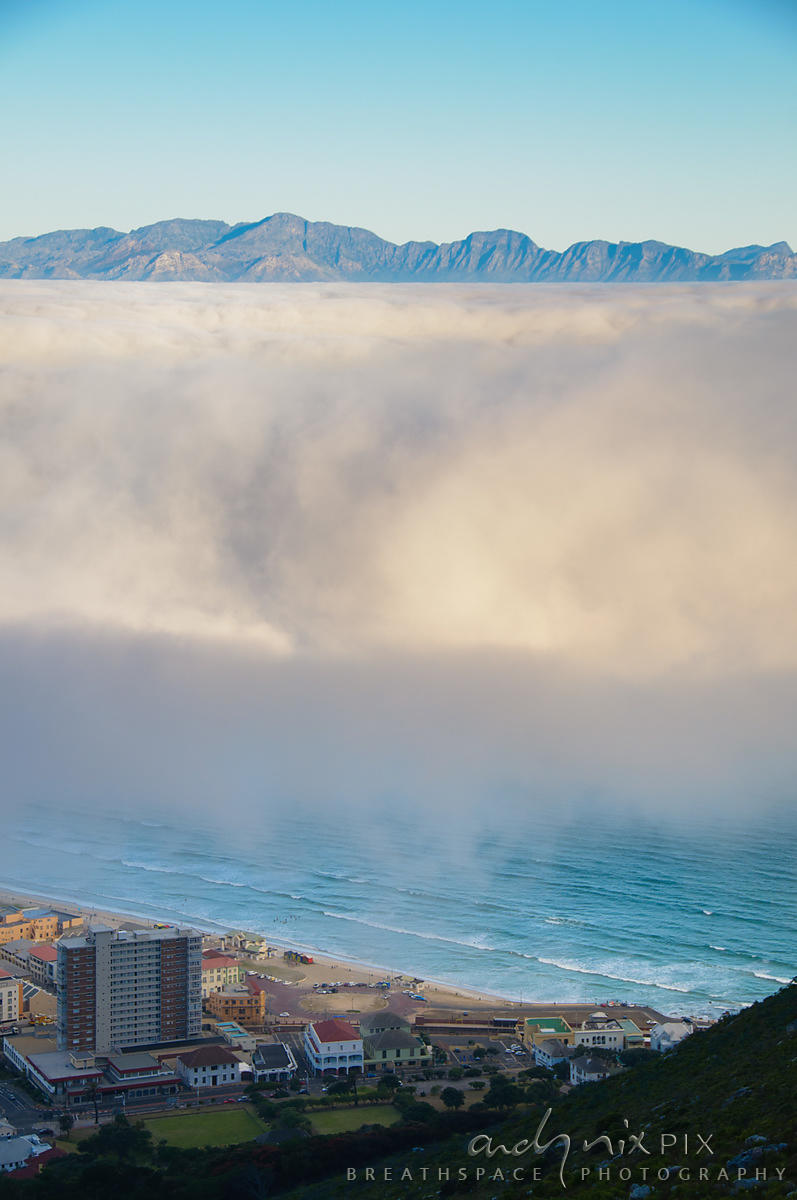 Fog over False Bay, sea and village at foot of mountain visable below cloud, distant mountains visable above cloud